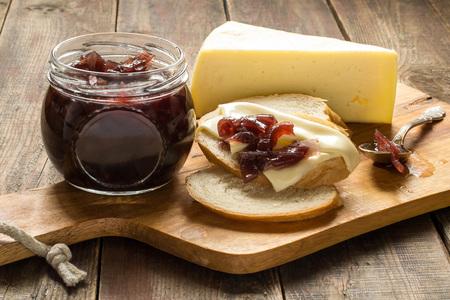 mermelada: Mermelada de cebolla, pan blanco con queso, un frasco de mermelada, un pedazo de queso en el tablero y una mesa de madera. Enfoque selectivo.