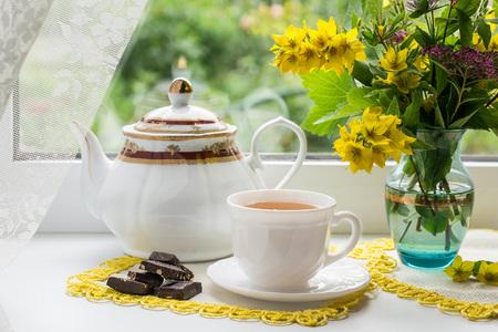'S ochtends thee in de buurt van het raam: een kopje thee, stukjes chocolade, waterkoker en een boeket bloemen in een vaas. Gezien door het glas zichtbare groene planten. Selectieve aandacht Stockfoto