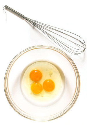 albumen: Whisk for whipping, three raw broken egg in a glass bowl on a white background Stock Photo
