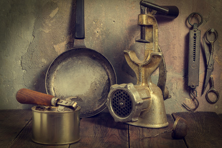 tea strainer: Lot of old kitchen utensils on a wooden table against a wall with cracked plaster (iron pan, mechanical grinder, tea strainer, spring balance, scissors, can opener, can. Toned photo