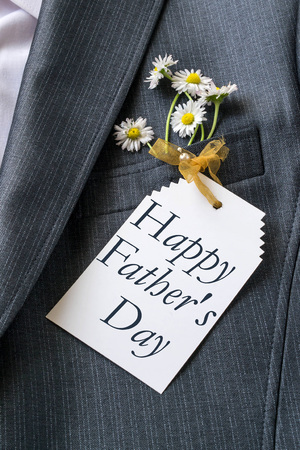 Congratulations to Fathers Day on the card and daisies in the pocket mens jacket Stock Photo