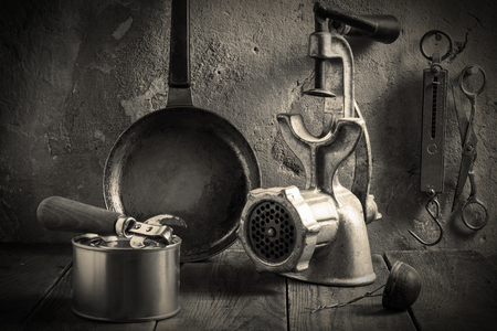steelyard: Outdated kitchen accessories: steel pan, mechanical chopper, steelyard, scissors, tea strainer, can opener, tin cans on wooden boards near the wall with an old plaster. Tinted photos