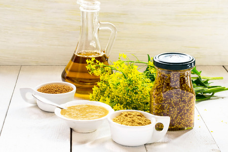 Different types of mustard: powder, seeds, cooked Dijon mustard, spicy Russian mustard, mustard oil, mustard flowers on a white wooden table. Selective focus