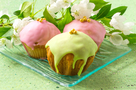 gritting: Tasty homemade cupcakes with pink and green frosting on a glass plate, a branch of apple blossoms on a green background. Selective focus Stock Photo