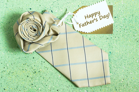 Card Fathers Day - a tie in the form of roses and label with the inscription: Happy Fathers Day on a green colored background Stock Photo