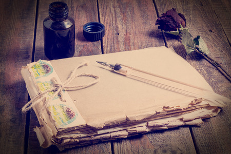 Symbols memories of the past: the old battered notebook, pen and ink in the bottle and dried rose on a wooden table. Tinted photos