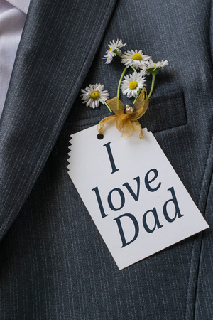 Mens jacket with the inscription on the card: I love dad and chamomile in a jacket pocket