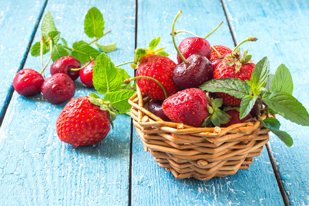 strawberry baskets: Fresh ripe strawberries and cherries in a wicker basket with mint on a blue painted wooden table. Selective focus Stock Photo