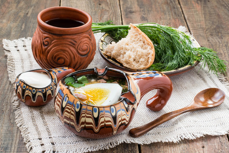 steins: Popular russian spring cold soup - okroshka with kvass. Okroshka in vintage painted bowl, sour cream, kvass in steins, wooden spoon, bread and dill on a plate. Selective focus Stock Photo
