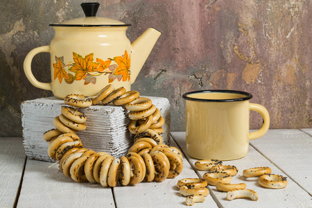 teaparty: Vintage yellow enamelware (teapot and Cup) and a bunch of small dry bagels with poppy seeds on a white wooden table on a background of cracked plaster wall Stock Photo