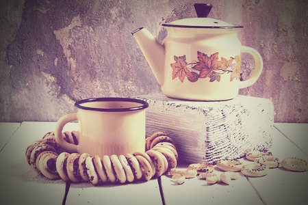 plaster board: Tea in rustic Russian style (retro): yellow enameled kettle on thick board, mug and a bunch of small dry bagels with poppy seeds on a white wooden table against the background of cracked plaster wall. Tinted photos