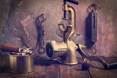 cocina vieja: Accesorios viejos de cocina: un helicóptero mecánica, Steelyard, tijeras, abrelatas, latas, colador de té en una mesa de madera cerca de la pared vieja con yeso agrietado. Estilo vintage. Fotos tintados