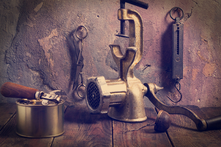 tea strainer: Old kitchen accessories: a mechanical chopper, steelyard, scissors, can opener, tin cans, tea strainer on a wooden table near old wall with cracked plaster. Vintage style. Tinted photos Stock Photo