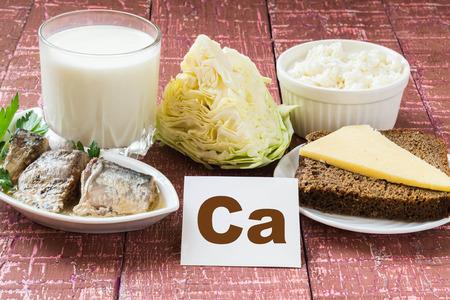 Producten - een bron van calcium (sardines in olie, kool, melk, kwark, bruin brood, kaas) op houten achtergrond van Bourgondië Stockfoto