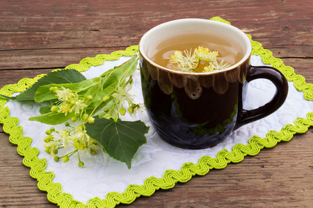 curative: Curative tea with linden flowers in a ceramic mug on a napkin with green trim and an old wooden table. Selective focus Stock Photo