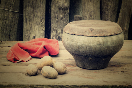 oven potatoes: Ancient pot - traditional utensils for cooking in the Russian oven, potatoes and a red rag on a old table in the garden near the fence. Tinted photos