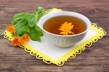 summer heat: Herbal medicine: fresh tea with calendula in a cup, marigold flowers on a napkin and a rustic wooden table. Selective focus Stock Photo