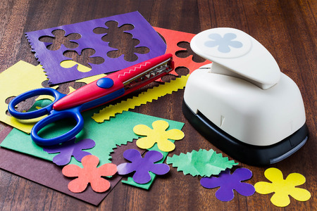 paper puncher: Shaped puncher, zigzag scissors, colored paper and design elements to create compositions on the wooden background. Selective focus
