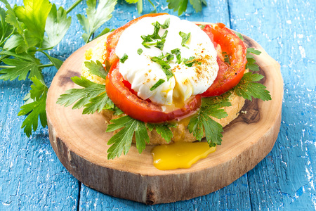 poach: Fresh poached egg on toast with tomato and parsley on a thick wooden plate on a blue wooden background