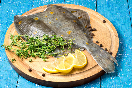 plaice: Fresh flounder with lemon, thyme and pepper on a round cutting board and blue wooden table Stock Photo
