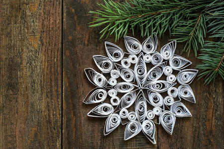 goodly: Goodly snowflake quilling technique on spruce branch on a wooden surface for the Christmas decoration with copy space Stock Photo