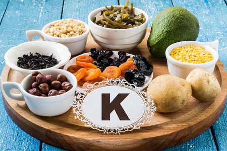 Products containing potassium (dried apricots, prunes, raisins, seaweed, avocado, lentils, potatoes, hazelnut, black tea, pine nuts) on a round cutting board and a blue wooden background
