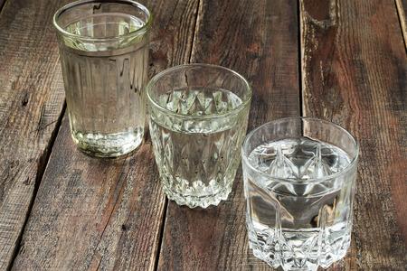 vasos de agua: Tres clases viejas gafas facetas vaso con agua sobre una mesa de madera