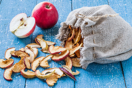 linen bag: Dried apples in a linen bag and fresh ripe apples on a blue painted table. Selective focus Stock Photo