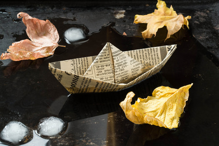 origami paper: Autumn mood: origami paper boat from old newspapers, yellow dry leaves in a puddle. Selective focus