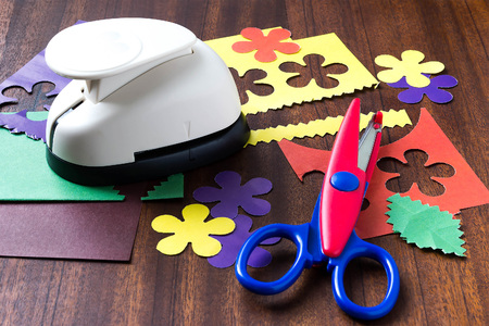 paper puncher: Detail and tools to create compositions of paper (puncher, zigzag scissors, colored paper, cut flowers) on a wooden background. Selective focus Stock Photo