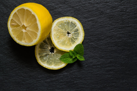 bactericidal: Slices and half fresh juicy lemon with mint leaves on a slate board Stock Photo