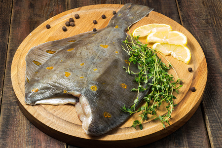 plaice: Raw plaice with pepper, thyme and lemon on a round cutting board and wooden table Stock Photo