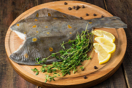 plaice: Fresh raw plaice with pepper, thyme and lemon on a round cutting board and wooden table
