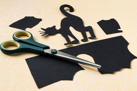 Preparing for Halloween - black cat cut out of paper. Silhouette of a cat, scissors and trim black paper on a yellow-pink background Stock Photo