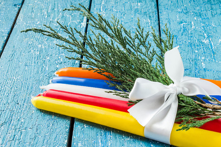mo�o blanco: Colorful holiday candles with coniferous branch and white bow on a blue wooden table Foto de archivo