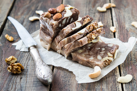 Chocolate Fudge with different kinds of nuts on wrapping paper. Selective focus