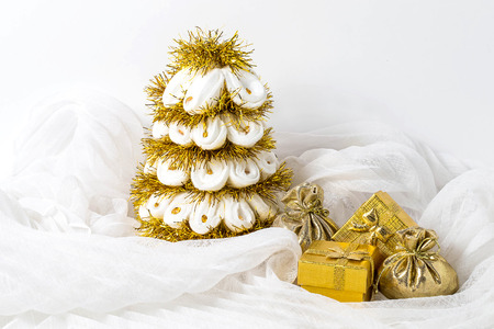 knack: Homemade white Christmas tree with tinsel and a box with gifts on a white background chiffon Stock Photo