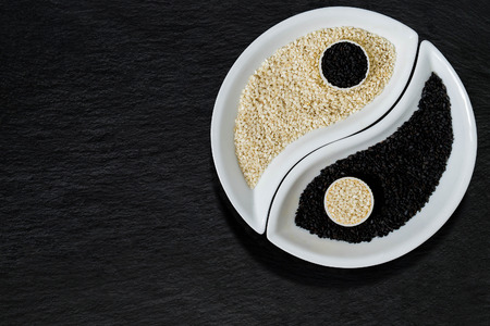 Oriental cuisine ingredients - black and white sesame seeds in the form of Yin Yang symbol