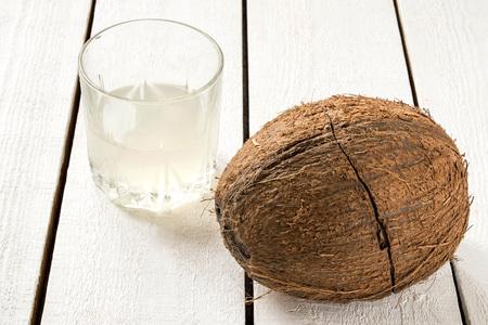Coconut mit Crack und Kokoswasser in einem Glas auf einem weißen Holztisch. Selektiver Fokus Lizenzfreie Bilder