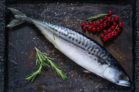 flesh colour: Preparing to bake mackerel with red currants and spices on an old scratched iron pan Stock Photo