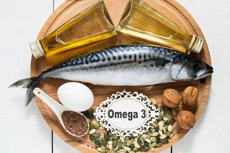 Produkte - Quelle Fettsäuren Omega 3 (Makrele, Leindotter Öl, Rapsöl, Bio-Ei, Kürbis und Leinsamen, Walnüsse) auf einem runden Holzbrett Standard-Bild - 49203727