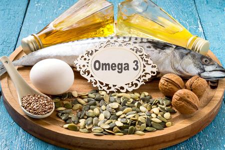 Produkte - Quelle Fettsäuren Omega 3 (Makrele, Leindotter Öl, Rapsöl, Bio-Ei, Kürbis und Leinsamen, Walnüsse) auf einem runden Holzbrett