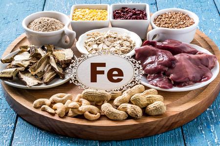 Erzeugnisse, die ferrum (getrocknete Pilze, Kleie, Buchweizen, Leber, Hartriegel, Cashew-Nüsse, Hafer, Linsen, Erdnüsse) auf einem runden Schneidebrett und einem blauen Holzuntergrund