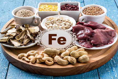 Products containing ferrum (dried mushrooms, bran, buckwheat, livers, dogwood, cashews, oats, lentils, peanuts) on a round cutting board and a blue wooden background Stockfoto