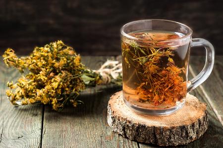 Tee mit nützlichen getrocknet Johanniskraut in einem Glaskrug auf einem Holztisch Frisch gebrühter. Selektiver Fokus