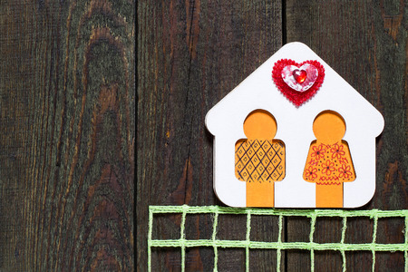 fidelity: Symbol of love and fidelity - hand-painted wooden house with little man and hearts on old wooden surface with space for text to the Valentines Day Stock Photo