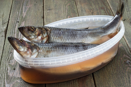 brine: Two salted herrings in plastic container with brine and spices on a wooden table