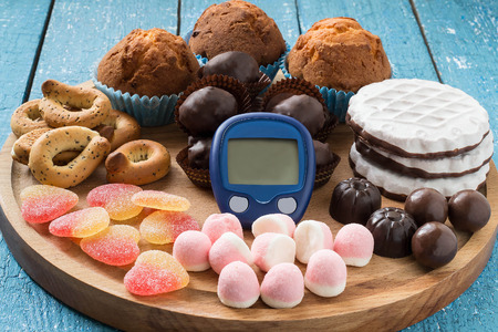 blood glucose: Different types of sweet foods, and a device for measuring blood glucose, sweet abuse, the threat of diabetes, the concept of limiting sweet Stock Photo