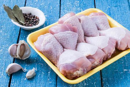Raw Hähnchenkeulen in einem Fach für das Kochen mit Knoblauch, Pfeffer und Lorbeerblatt auf einem blauen Holztisch