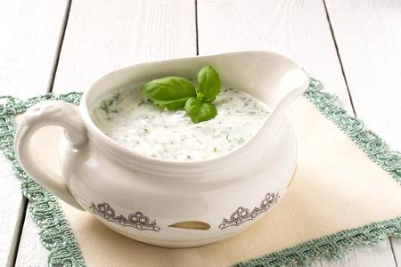 tzatziki: Greek Tzatziki sauce with yogurt, cucumbers, garlic and dill on a white wooden table